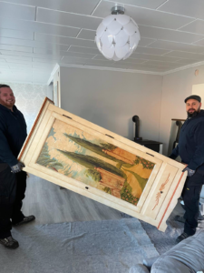 Nordsee Umzüge Mitarbeiter tragen Schrank